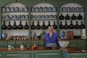 Apothecary Sharon Cotner stands in front of antique drug jar collection in the Pasteur & Galt Apothecary. (Photograph by Fred Blystone; courtesy of Colonial Williamsburg Foundation).