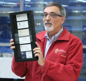 Greg Higby holds a framed case featuring his business cards over the years.