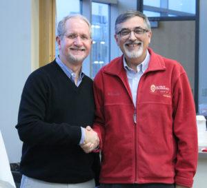 AIHP Executive Director-designate Dennis Birke (left) shakes hands with AIHP Executive Director Greg Higby.