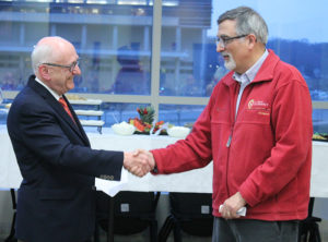 AIHP President William Zellmer shakes hands with AIHP Executive Director Gregory Higby at Higby's retirement party in 2018.