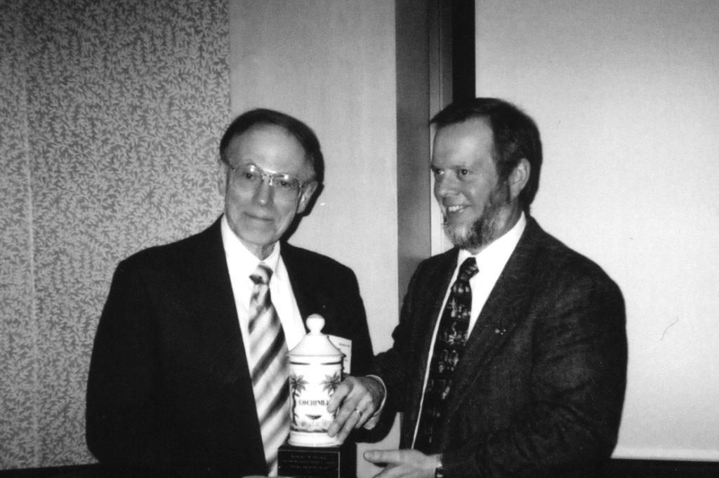 Bob Buerki (left) receives the 2004 Edward Kremers Award from W. Clarke Ridgway.